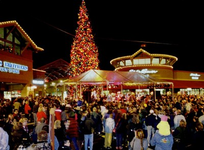 Crowd looking at Christmas tree at night in retail area
